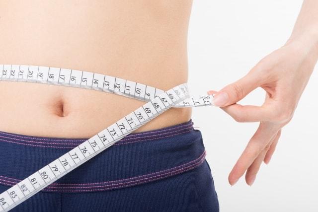 お腹周りを測る女性
