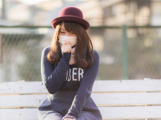 マスクし咳をする女性