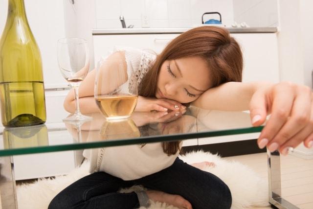 お酒を飲んで居眠りする女性